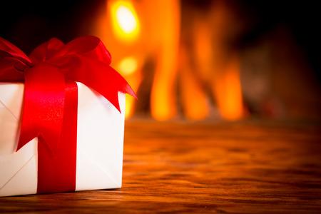 Foto de Christmas gift box on wood table against fireplace. Winter holiday concept - Imagen libre de derechos