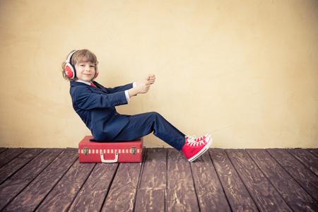 Photo pour Portrait of child businessman with suitcase. Business trip and summer travel concept - image libre de droit
