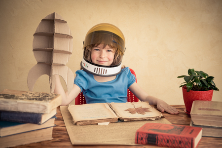 Photo for Kid astronaut with cardboard toy rocket. Child playing at home. Earth day concept - Royalty Free Image