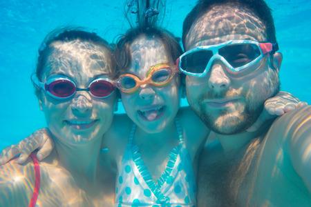 Foto de Family having fun in swimming pool. Underwater funny portrait. Summer vacation - Imagen libre de derechos