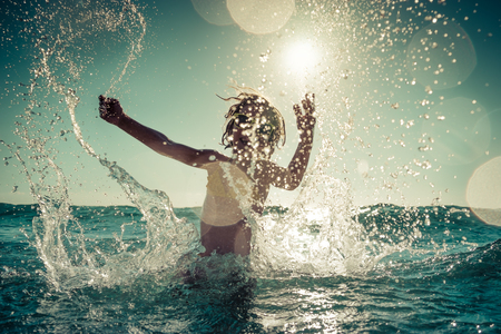 Photo for Happy child playing in the sea. Kid having fun outdoors. Summer vacation and healthy lifestyle concept. Toned image - Royalty Free Image