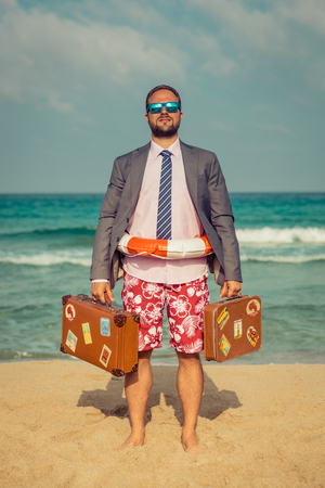 Foto de Portrait of funny businessman on the beach. Man having fun by the sea. Summer vacation and travel concept - Imagen libre de derechos