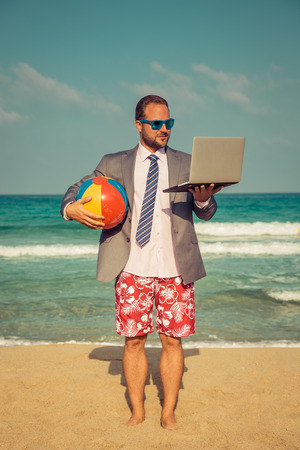 Foto de Portrait of funny businessman on the beach. Man having fun by the sea. Summer vacation and travel concept - Imagen libre de derechos