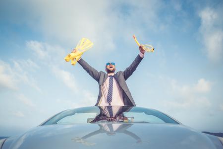 Foto de Successful young businessman on a beach. Man standing in the cabriolet classic car. Summer vacations and travel concept - Imagen libre de derechos