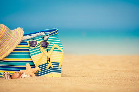 Photo pour Flip-flops and bag on sandy beach against blue sea and sky background. Summer vacation concept - image libre de droit