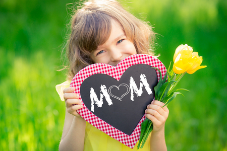 Foto für Child holding card blank and bouquet of flowers against green background. Spring family holiday concept. Mother's day - Lizenzfreies Bild