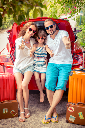 Photo for Happy family ready to trip. People standing near red car. Summer vacation and travel concept - Royalty Free Image