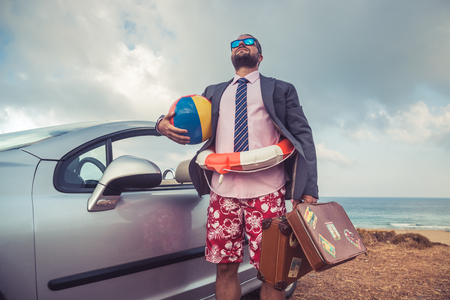 Foto per Successful young businessman on a beach. Man standing near cabriolet classic car. Summer vacations and travel concept - Immagine Royalty Free