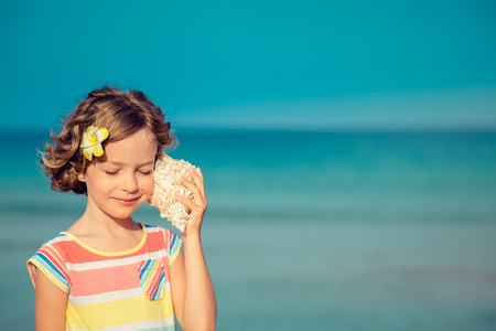 Child relaxing on the beach against sea and sky background. Summer vacation and travel conceptの写真素材