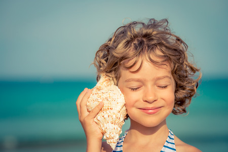 Child relaxing on the beach against sea and sky background. Summer vacation and travel concept