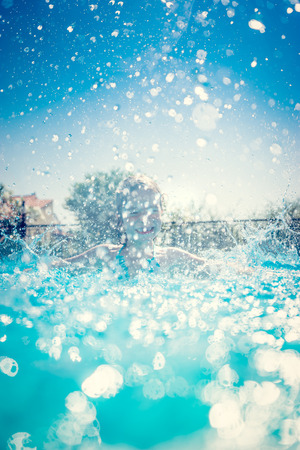 Photo for Child having fun in swimming pool. Kid playing outdoors. Summer vacation and healthy lifestyle concept - Royalty Free Image
