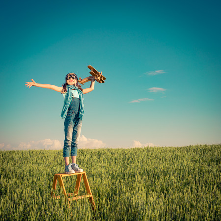 Foto de Happy child playing with toy airplane outdoors. Kid in summer field. Travel and vacation concept. Imagination and freedom - Imagen libre de derechos