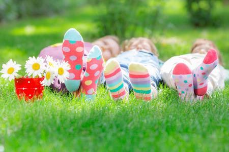 Foto de Group of happy children playing outdoors. Kids having fun in spring park. Friends lying on green grass - Imagen libre de derechos