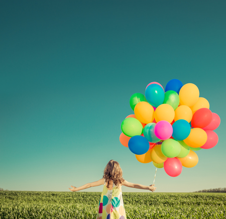 Foto de Happy child playing with bright multicolor balloons outdoor. Kid having fun in green spring field against blue sky background. Summer vacation and travel concept - Imagen libre de derechos