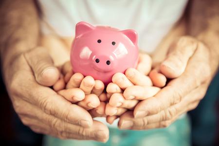 Photo pour Family holding piggybank in hands. Investment concept - image libre de droit