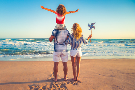 Photo pour Happy family on the beach. People having fun on summer vacation. Father, mother and child against blue sea and sky background. Holiday travel concept - image libre de droit