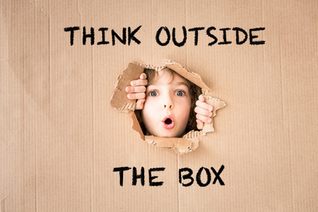 Photo pour Surprised child looking through hole of cardboard. Think outside the box text - image libre de droit