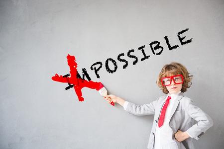 Foto de Child pretend to be businessman. Kid erasing text impossible. Imagination, idea and success concept. Copy space for your text - Imagen libre de derechos