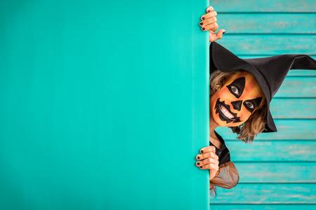 Foto de Funny child dressed witch costume. Happy kid painted terrible pumpkin holding banner blank. Halloween autumn holiday concept - Imagen libre de derechos
