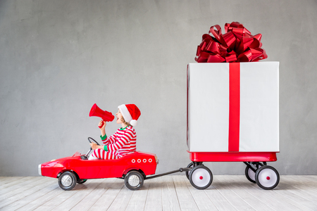 Photo pour Happy child with Christmas gift. Kid having fun at home. Xmas holiday concept - image libre de droit