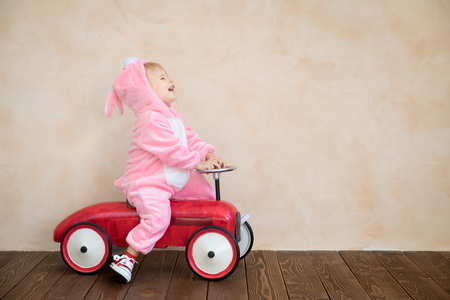 Photo for Funny kid wearing Easter bunny. Child riding toy car at home. Spring holidays concept - Royalty Free Image
