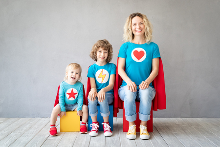 Foto de Family of superheroes playing at home. Mother, daughter and son having fun together. Parents with children pretend to be a super heroes - Imagen libre de derechos