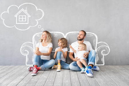 Photo pour Happy family with two kids playing into new home. Father, mother and children having fun together. Moving house day and real estate concept - image libre de droit