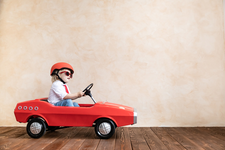 Foto de Happy child playing at home. Funny kid driving toy car indoor. Success and win concept - Imagen libre de derechos