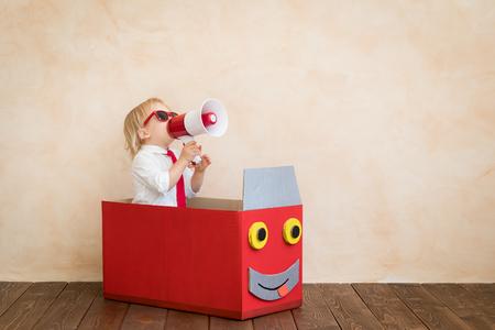 Foto de Happy child pretend to be businessmen. Funny kid speaking by megaphone. Education, start up and business idea concept - Imagen libre de derechos