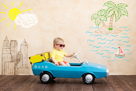 Foto de Happy child riding toy vintage car. Funny kid playing at home. Summer vacation and travel concept - Imagen libre de derechos