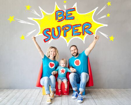 Photo pour Family of superheroes playing at home. Father, mother and kid having fun together. Parents with child pretend to be a super heroes - image libre de droit