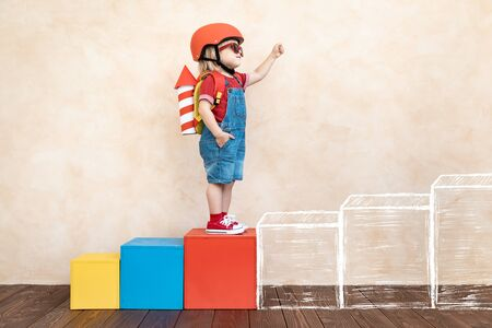 Kid with toy paper rocket. Child playing at home. Success, imagination and innovation technology concept