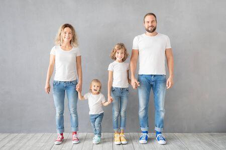 Foto de Happy family standing against grey background. Parents with children having fun at home. Portrait of father, mother, daughter and son - Imagen libre de derechos