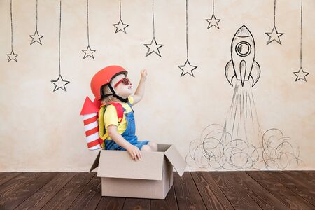 Photo for Kid with toy paper rocket. Child playing at home. Success, imagination and innovation technology concept - Royalty Free Image