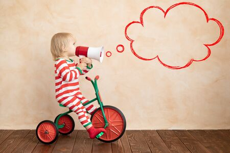 Photo pour Happy child dressed Santa Claus costume playing at home. Funny kid driving toy car and speaking by megaphone. Christmas holiday concept - image libre de droit
