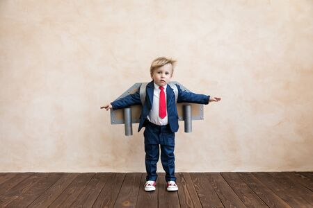 Photo pour Portrait of young businessman with toy paper wings. Happy child playing at home. Kid having fun. Success, creative and start up concept - image libre de droit
