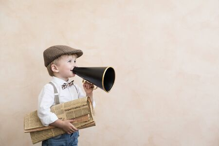 Photo for Child holding loudspeaker and newspaper. Kid shouting through vintage megaphone. Business news concept - Royalty Free Image