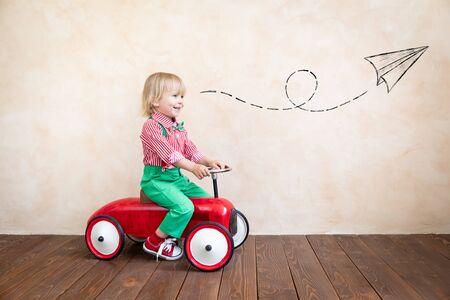 Photo pour Happy child riding vintage car. Kid having fun at home. Imagination and childhood concept - image libre de droit