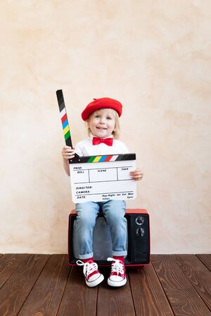 Photo for Funny kid holding clapper board. Happy child having fun at home. Retro cinema concept - Royalty Free Image