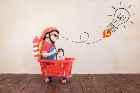 Foto de Kid with toy paper rocket. Child playing at home. Success, imagination and innovation technology concept - Imagen libre de derechos