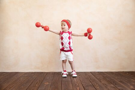Photo pour Happy child playing at home. Funny kid wants to become a sportsman. Healthy lifestyle concept - image libre de droit