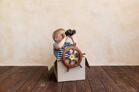 Photo pour Happy child dreams of becoming a captain. Kid having fun at home. Boy wearing striped shirt playing in cardboard box. Summer vacation and travel concept. Dream and imagination - image libre de droit