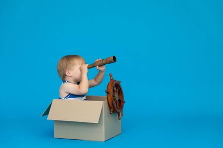 Photo pour Happy child dreams of becoming a captain. Kid having fun against blue background. Boy wearing striped shirt playing in cardboard box. Summer vacation and travel concept. Dream and imagination - image libre de droit