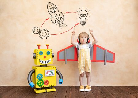 Photo pour Happy child with cardboard wings. Funny kid playing with toy handmade robot. Success, creative and innovation technology concept - image libre de droit