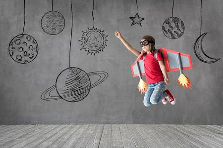 Photo pour Happy child with toy paper wings playing at home. Kid having fun. Success, creative and start up concept - image libre de droit