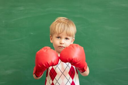Photo pour Funny child student wearing red boxing gloves in class. Happy kid against green chalkboard. Physical education concept. Back to school - image libre de droit