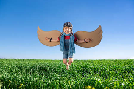 Photo for Happy child playing with toy wings against blue sky background. Kid having fun outdoor in spring green field. Imagination and children dream concept - Royalty Free Image