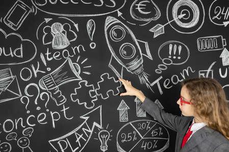 Photo pour Young businesswoman against chalkboard with business sketch. Success marketing plan and startup concept - image libre de droit