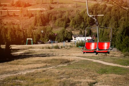 Close up of red chairlift going over trees in summer on Mountain. Carpathian national park