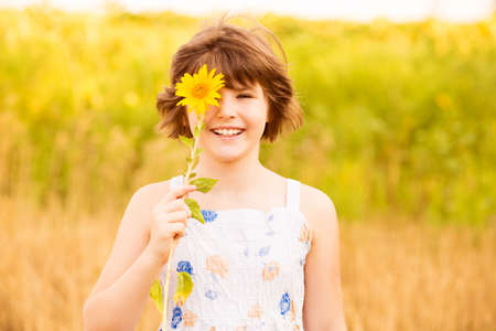 Photo for Joyful girl smiling and covering face with sunflower in summer field - Royalty Free Image